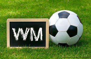 Fussball auf grüner Wiese mit Tafel auf der WM steht